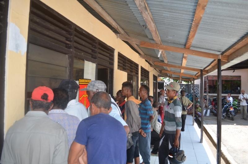 Warga Desa Tohe sedang menunggu sambil mengamati pemeriksaan sejumlah saksi, terkait dugaan penggelapan dana raskin desa tersebut.