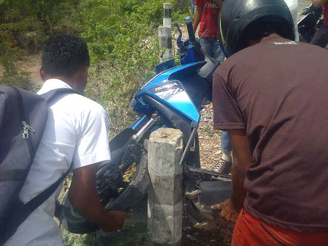 Tampak warga sedang mengevakuasi sepeda motor milik Efen.