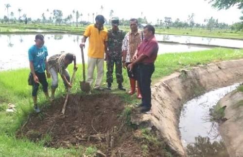 Tampak Sekretaris Dinas PU Malaka, Camat Malaka Tengah, anggota Koramil Betun dan masyarakat perbaiki irigasi yang rusak.