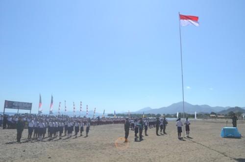 Satgas Pamtas RI-RDTL dan masyarakat upacara bendera di pantai perbatasan RI-RDTL.