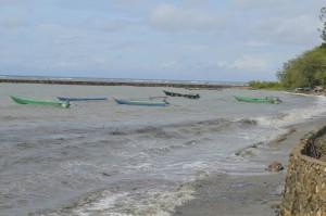 Perahu nelayan hanya ditambatkan di pantai akibat gelombang tinggi.